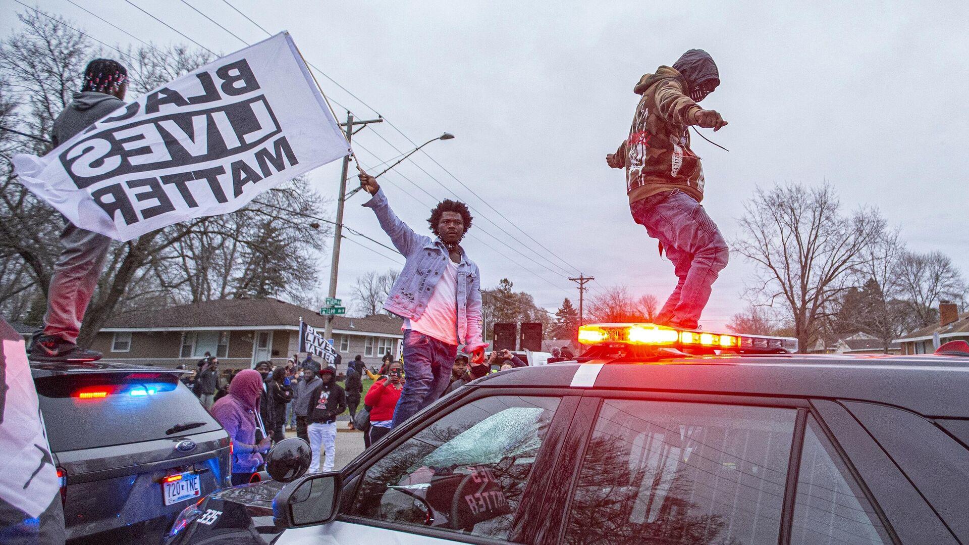 Участники акции протеста на капоте полицейского автомобиля в центре города Бруклин-Сентер в штате Миннесота, США - РИА Новости, 1920, 14.04.2021