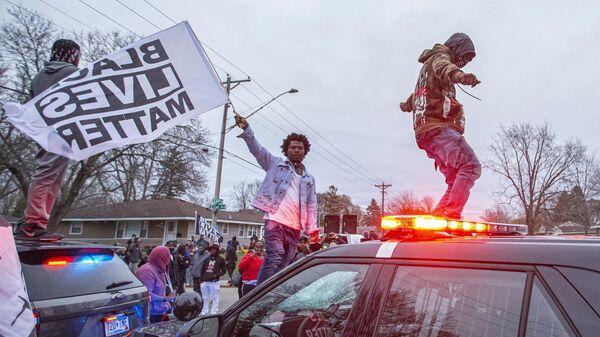 Участники акции протеста на капоте полицейского автомобиля в центре города Бруклин-Сентер в штате Миннесота, США