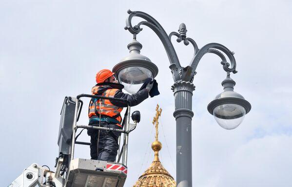 Сотрудник коммунальной службы протирает плафон фонаря наружного освещения на Пречистенской набережной в Москве
