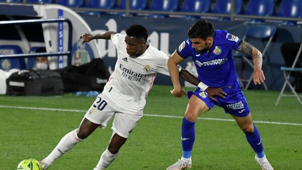 Real Madrid's Brazilian forward Vinicius Junior (L) vies with Getafe's Uruguayan midfielder Mauro Arambarri during the Spanish League football match between Getafe CF and Real Madrid CF at the Col. Alfonso Perez stadium in Getafe on April 18, 2021. (Photo by PIERRE-PHILIPPE MARCOU / AFP)