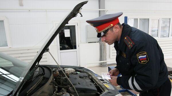 Сотрудник ГИБДД проводит технический осмотр автотранспорта