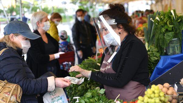 Посетительница и продавец на продовольственной ярмарке выходного дня