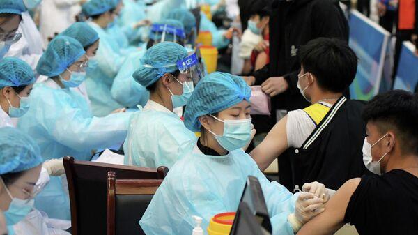 Медицинские работники во время вакцинации пациентов от коронавируса в университете в Циндао