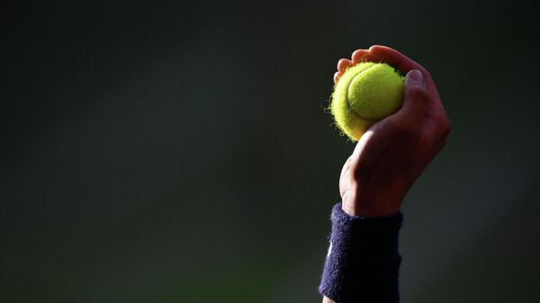 A ballboy holds up a ball as Spain's Rafael Nadal plays Switzerland's Roger Federer during their men's singles semi-final match on day 11 of the 2019 Wimbledon Championships at The All England Lawn Tennis Club in Wimbledon, southwest London, on July 12, 2019. (Photo by Daniel LEAL-OLIVAS / AFP) / RESTRICTED TO EDITORIAL USE