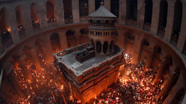 Православные верующие держат свечи, зажженные от Благодатного огня, в Храме Гроба Господня в Иерусалиме 27 апреля 2019 года