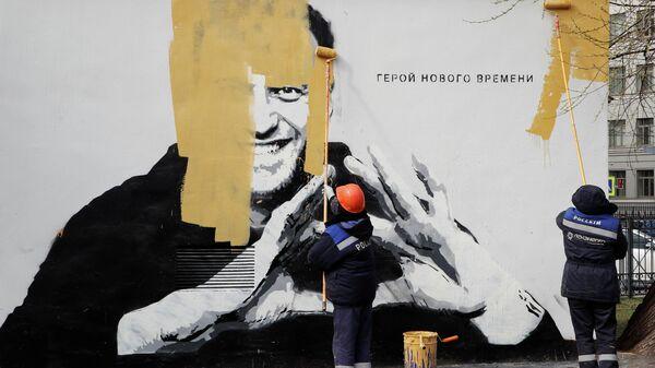 Коммунальные работники закрашивают граффити с изображением Алексея Навального в Санкт-Петербурге