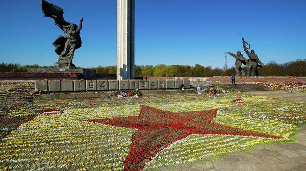 Красная звезда, выложенная волонтерами из цветов, возложенных к памятнику Освободителям в Парке Победы в Риге