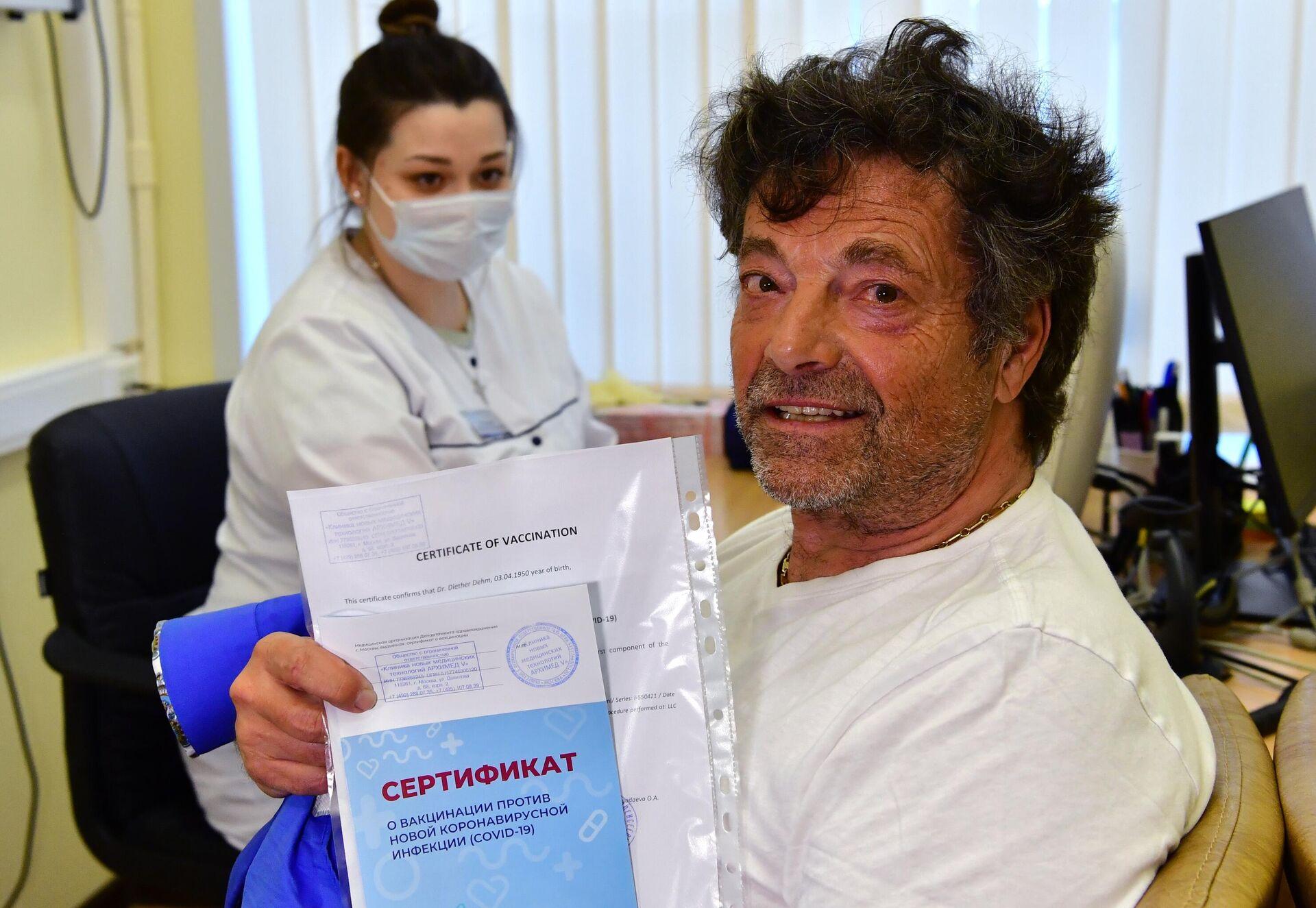 Немецкий депутат Дитер Дэм держит в руке сертификат о прививке против коронавируса после вакцинации от COVID-19 российским препаратом Sputnik V  - РИА Новости, 1920, 10.05.2021