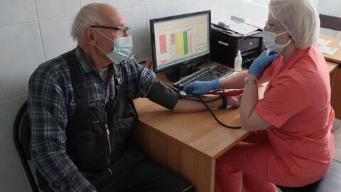 Медицинский работник проводит медосмотр пациента перед вакцинацией от коронавирусной инфекции
