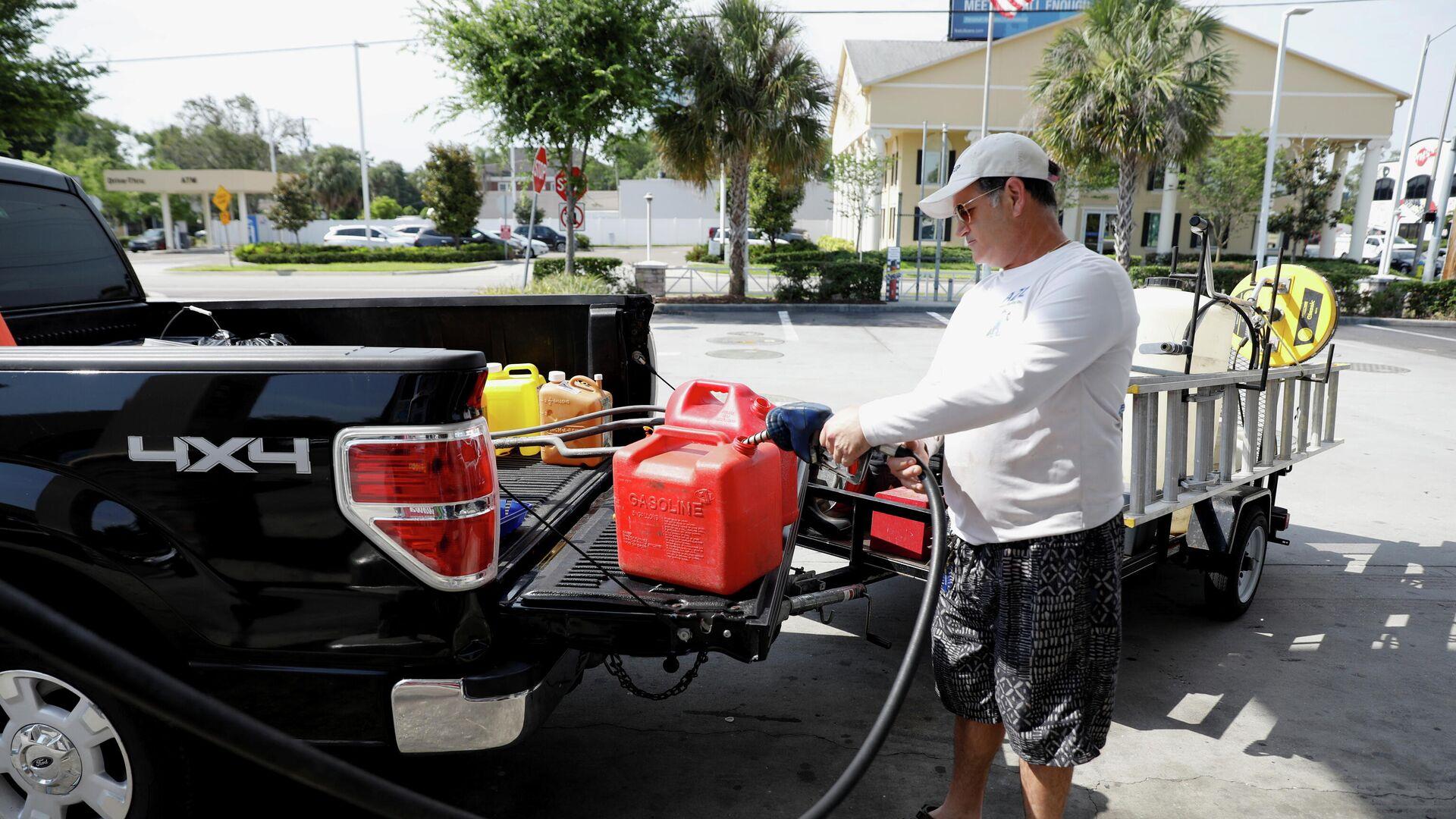 Мужчина наполняет канистры топливом после кибератаки на трубопровод компании Colonial Pipeline в Тампе, Флорида, США - РИА Новости, 1920, 13.05.2021