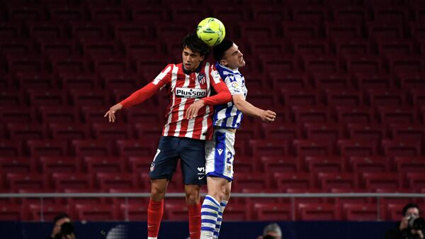 Atletico Madrid's Portuguese midfielder Joao Felix (L) jumps for the ball with Real Sociedad's Spanish forward Ander Barrenetxea during the Spanish league football match Club Atletico de Madrid against Real Sociedad at the Wanda Metropolitano stadium in Madrid on May 12, 2021. (Photo by PIERRE-PHILIPPE MARCOU / AFP)