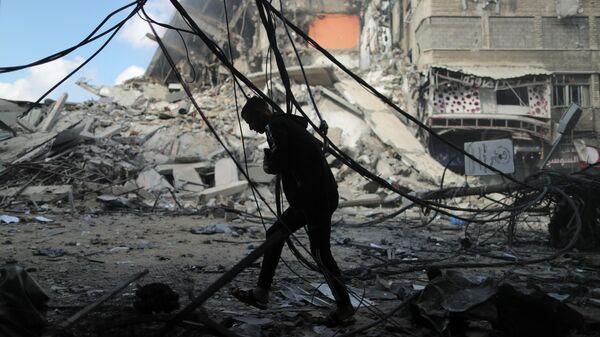 Палестинец бежит в укрытие во время израильского авиаудара в городе Газа