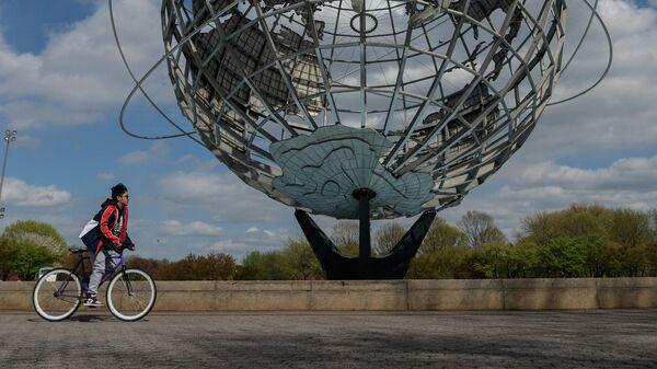 Мальчик проезжает на велосипеде мимо изображения Земли