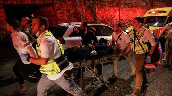 Cпасатели несут раненного во время обрушения трибуны синагоги в Гиват-Зееве, Израиль
