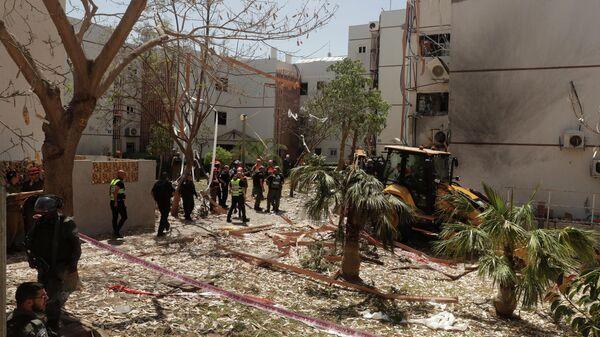 Израильские спасатели возле жилого дома в Ашдоде, пострадавшего в результате попадания в него ракеты, выпущенной из сектора Газа, Израиль