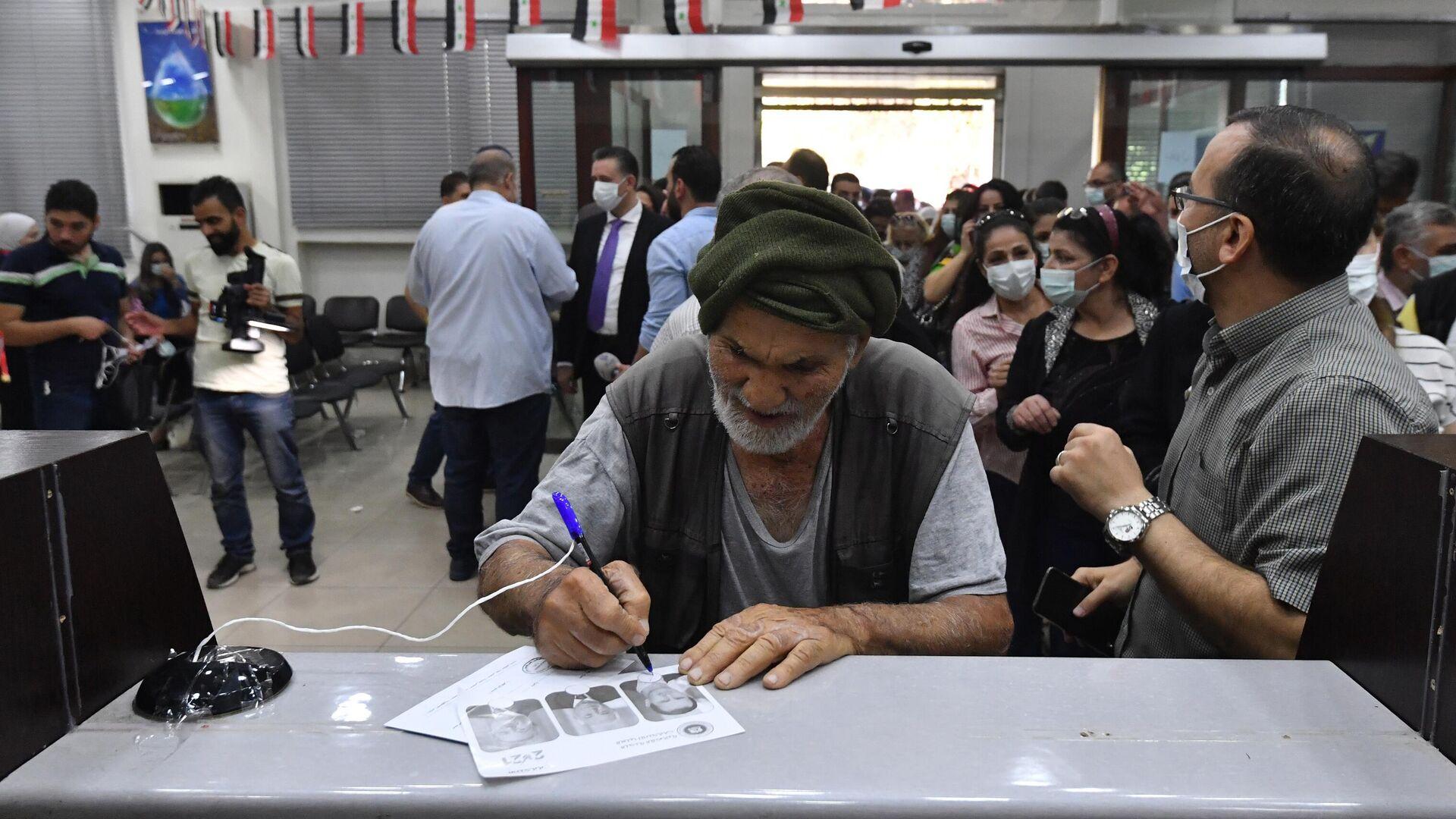Мужчина голосует на выборах президента Сирии на одном из избирательных участков Дамаска - РИА Новости, 1920, 27.05.2021