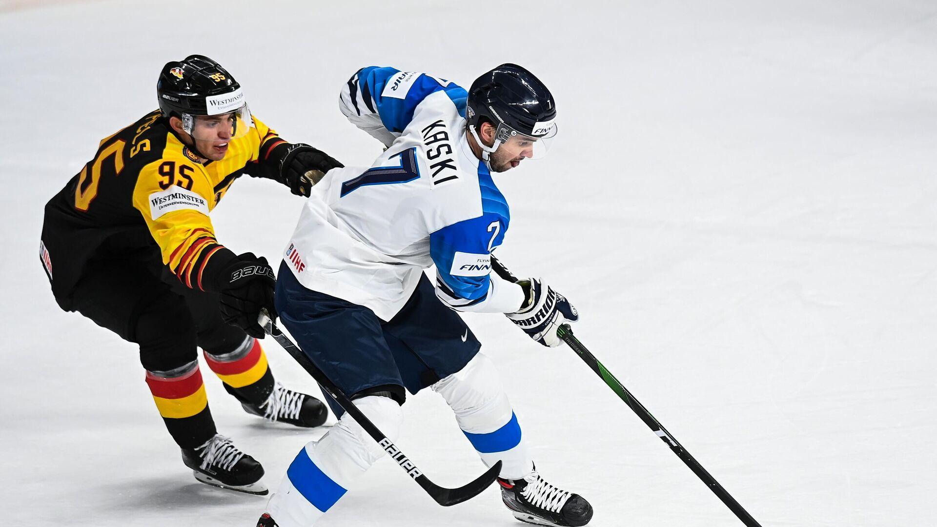Слева направо: Фредерик Тиффельс (Германия) и Оливер Каски (Финляндия) в матче группового этапа чемпионата мира по хоккею 2021 между сборными командами Германии и Финляндии. - РИА Новости, 1920, 05.06.2021