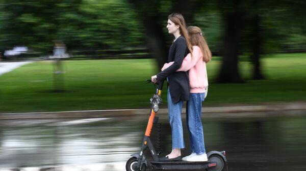 Девушки едут на электросамокате в центре Москвы