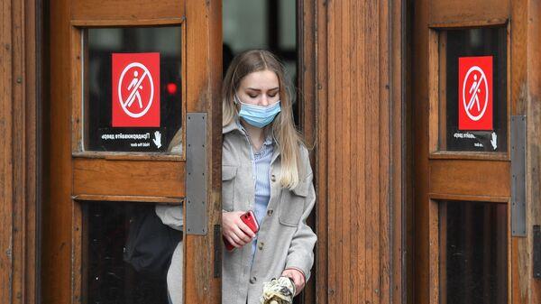 Женщина в маске выходит из метро в Москве