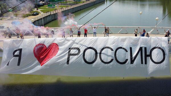 Участники акции в честь Дня России на Мосту Поцелуев в Краснодаре с баннером Я люблю Россию
