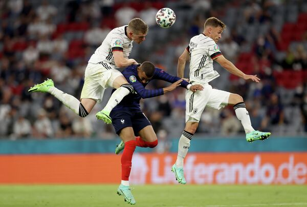 Защитник сборной Германии Маттиас Гинтер, нападающий сборной Франции Килиан Мбаппе и полузащитник сборной Германии Йосуа Киммих (слева направо)