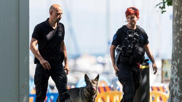 Полицейские со служебной собакой во время саммита президента России Владимира Путина и президента США Джо Байдена