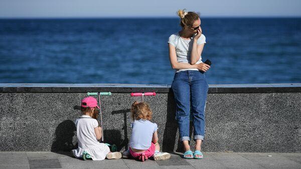 Девушка с детьми на набережной