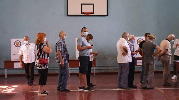 Люди в одном из избирательных участков во время досрочных парламентских выборов в Армении