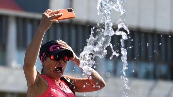 Женщина у фонтана в Парке искусств Музеон в Москве в жаркую погоду