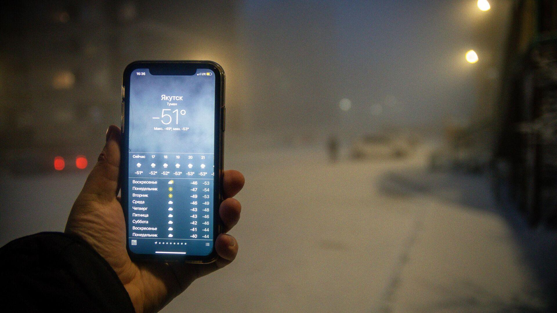 Мужчина демонстрирует мобильный телефон с информацией о прогнозе погоды  - РИА Новости, 1920, 22.06.2021