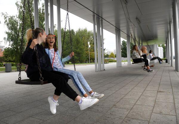 Девушки качаются на качелях в парке 850-летия Москвы на территории района Марьино