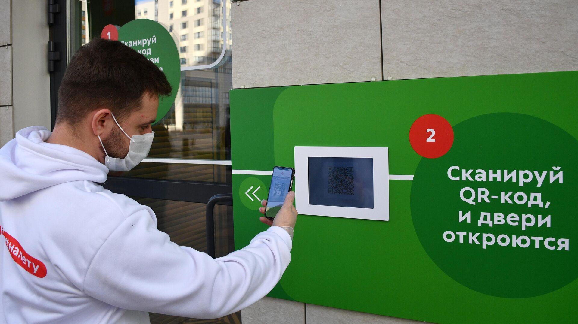Молодой человек в защитной маске сканирует QR-код с помощью смартфона на входе в магазин - РИА Новости, 1920, 24.06.2021
