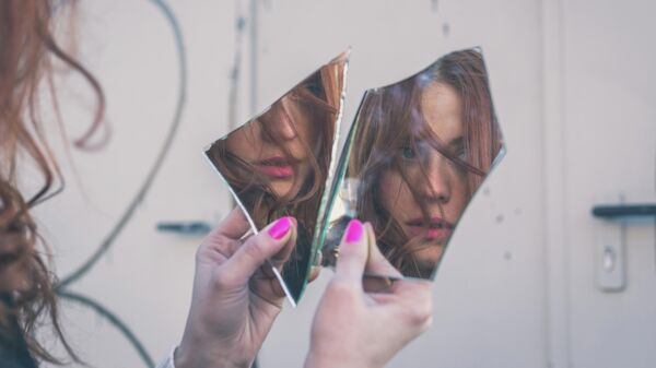 Девушка смотрится в разбитое зеркало