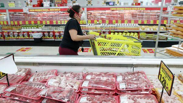 Покупательница в маске проходит через мясные ряды в продуктовом магазине