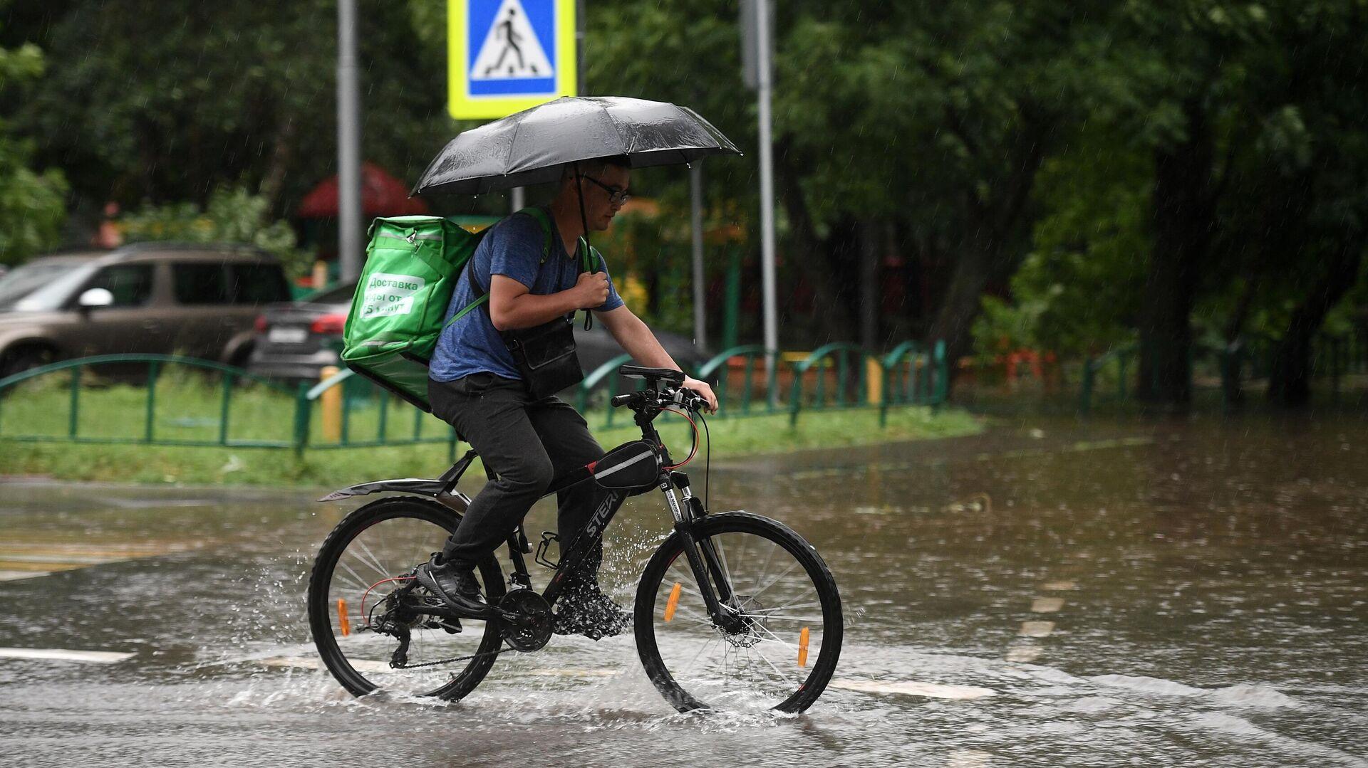 Мужчина едет на велосипеде по одной из улиц в Москве во время дождя - РИА Новости, 1920, 02.08.2021