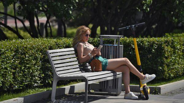 Девушка со смартфоном в парке