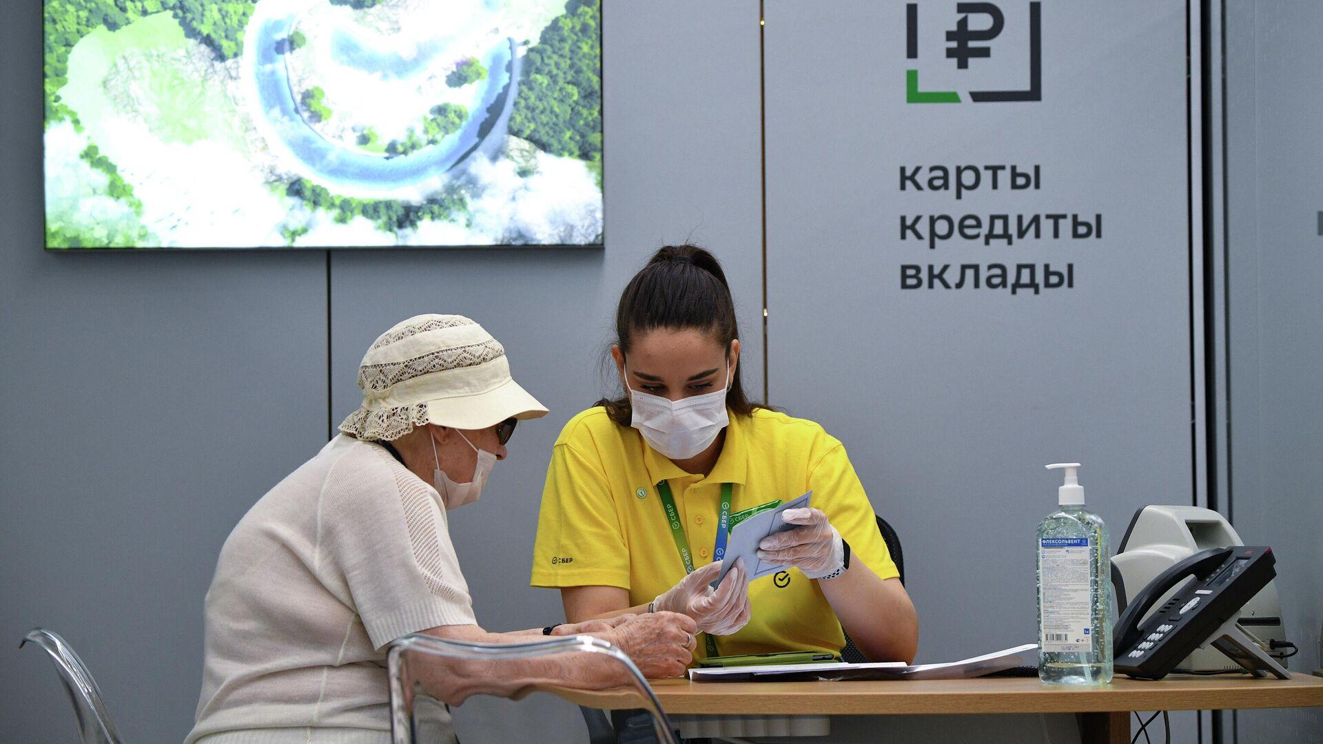 Сотрудница офиса Сбербанка нового формата, открывшегося на Красном проспекте в Новосибирске, во время работы с клиентом - РИА Новости, 1920, 21.07.2021