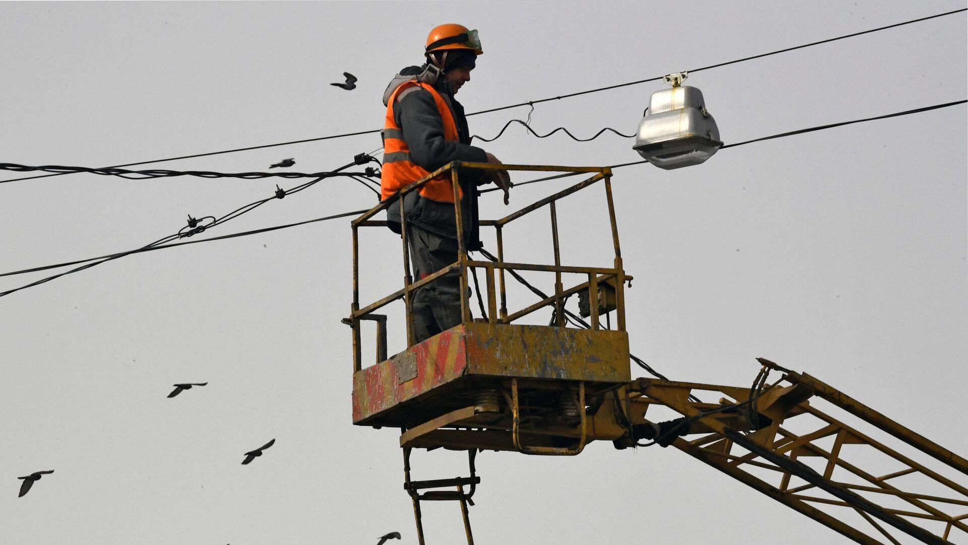 Работник коммунальной службы ремонтирует фонарь - РИА Новости, 1920, 09.07.2021