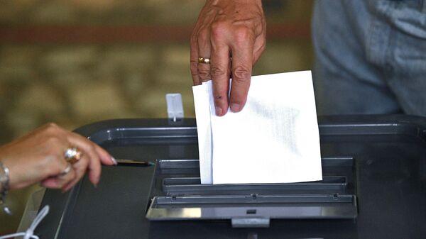 Мужчина голосует на избирательном участке в Кишиневе во время досрочных парламентских выборов в Молдавии