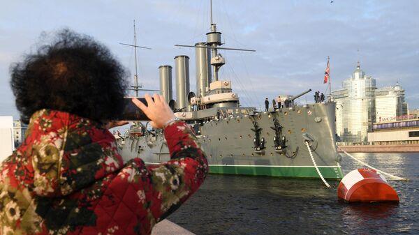 Туристка фотографирует музей Крейсер Аврора в Санкт-Петербурге