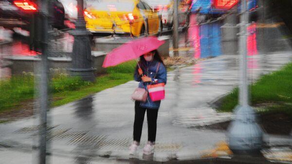 Девушка под зонтом у пешеходного перехода во время дождя