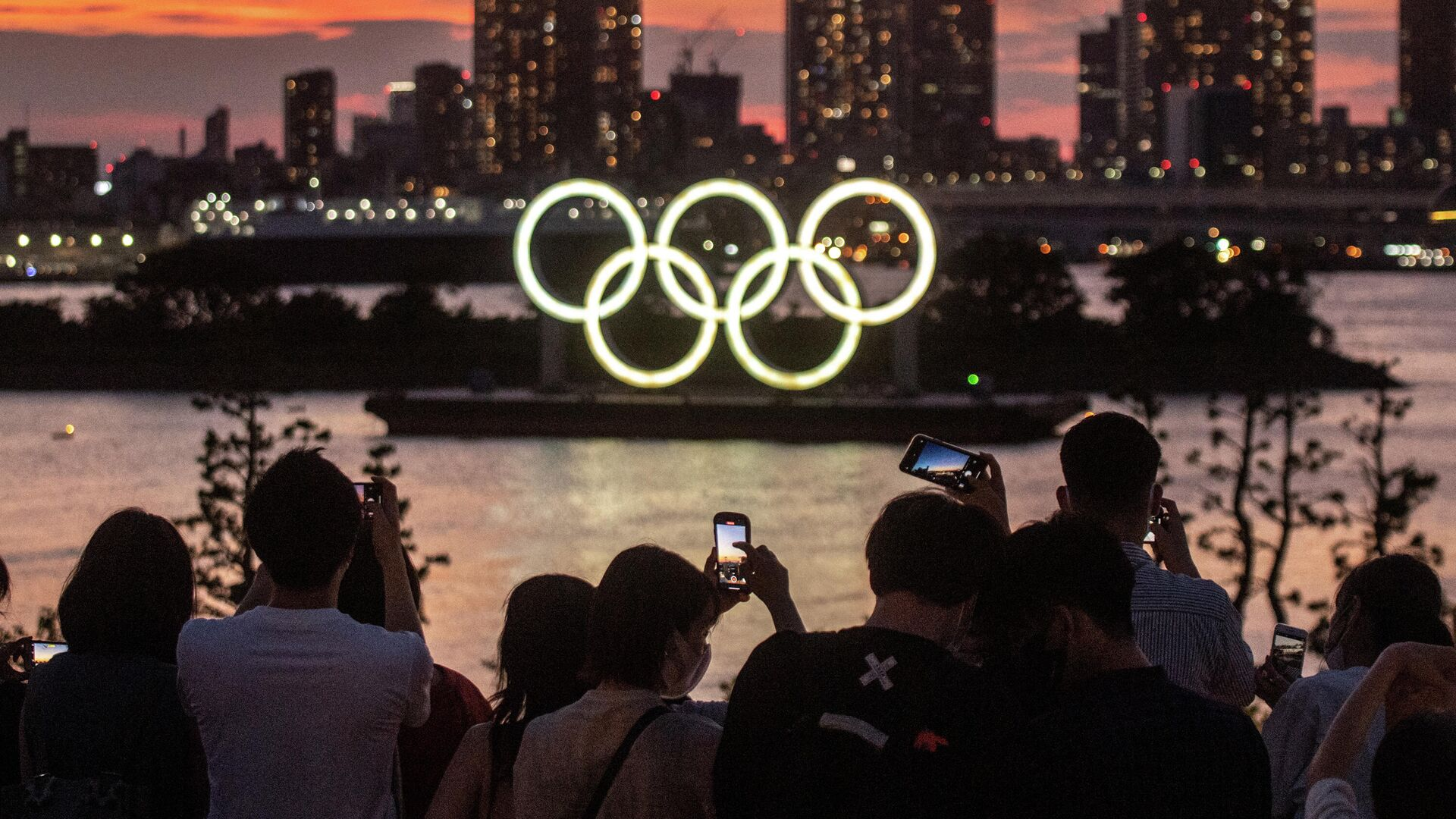People take pictures as the Olympic rings lit up at dusk on the Odaiba waterfront in Tokyo on July 22, 2021 on the eve of the start of the Tokyo 2020 Olympic Games. (Photo by Philip FONG / AFP) - РИА Новости, 1920, 22.07.2021