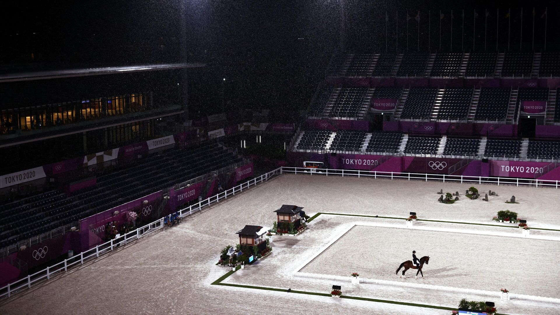 Russia's Aleksandra Maksakova rides Bojengels under the rain in the dressage individual grand prix group C during the equestrian competition of the Tokyo 2020 Olympic Games at the Equestrian Park in Tokyo on July 24, 2021. (Photo by Behrouz MEHRI / AFP) - РИА Новости, 1920, 25.07.2021