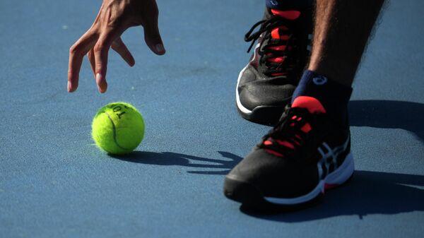 Волонтер подает теннисный мяч на Олимпиаде в Токио