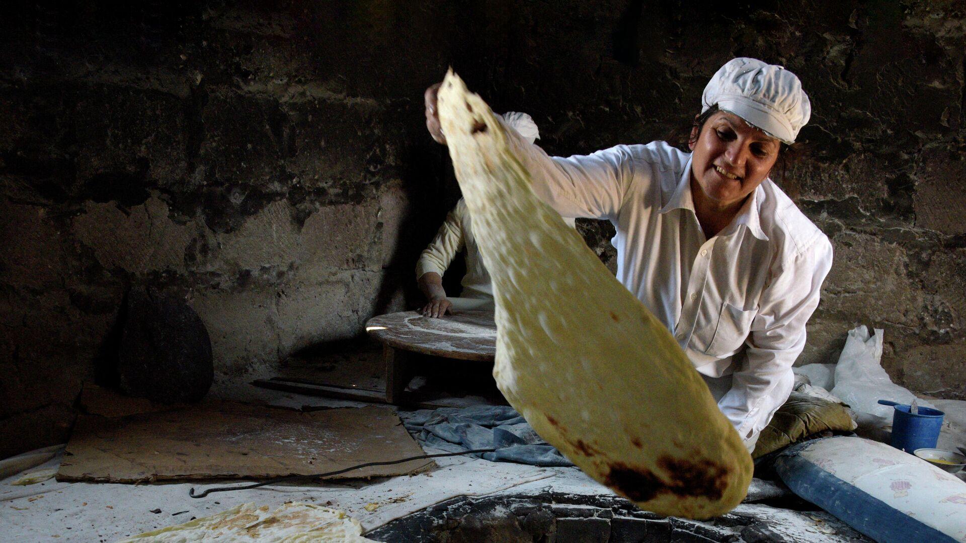 Женщина вынимает готовый лаваш из тандыра  - РИА Новости, 1920, 27.07.2021