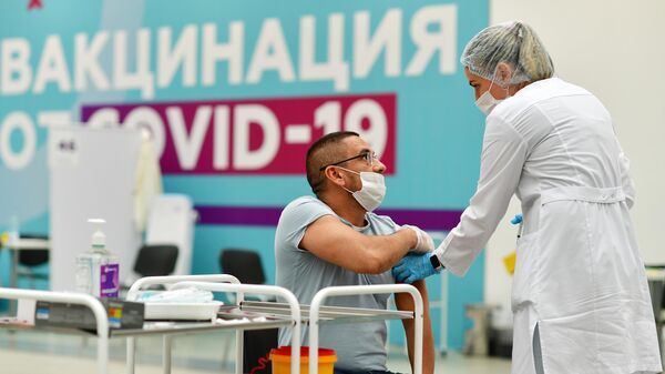 Посетитель делает прививку в центре вакцинации от COVID-19 в Гостином дворе в Москве