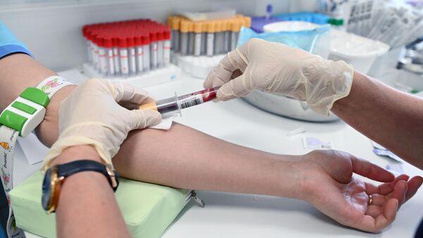 Медицинский работник проводит забор крови на антитела к коронавирусу COVID-19