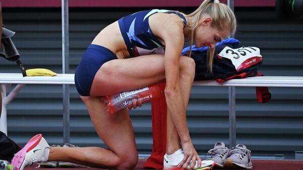 Россиянка Дарья Клишина прижимает лед к ноге на соревнования по прыжкам в длину на Олимпиаде в Токио