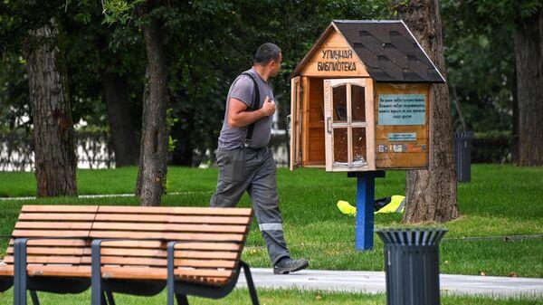 Уличная библиотека в парке Декабрьского восстания рядом со станцией метро Улица 1905 года и рабочий во время благоустройства парка