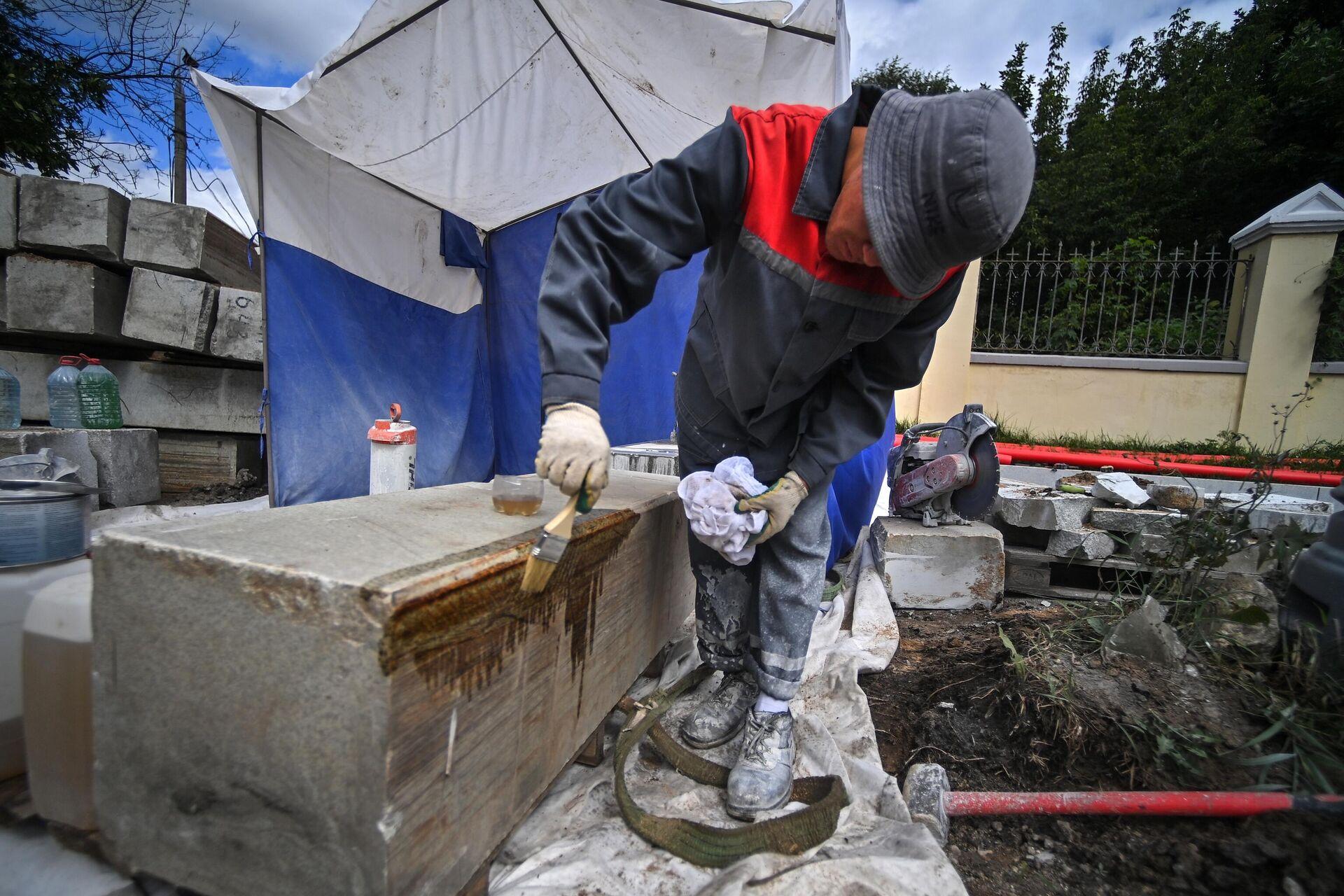 Рабочий во время работ по восстановлению бордюрного камня вдоль ограды Ваганьковского кладбища со стороны Звенигородского шоссе - РИА Новости, 1920, 09.08.2021